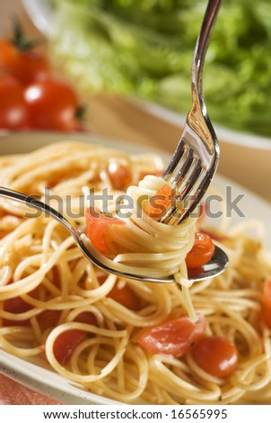 fresh spaghetti on fork and spoon close up shoot - stock photo