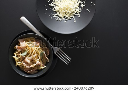 Fresh Spaghetti with prosciutto and parmesan on black background - stock photo
