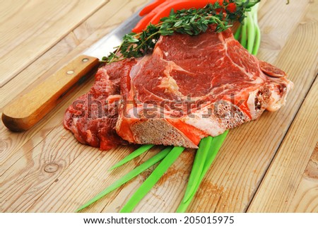 fresh spare ribs : raw lamb with thyme , red chili pepper , and green onion on wooden board - stock photo