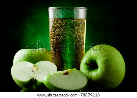 Fresh sparkling green apple juice on green spot lighted background - stock photo