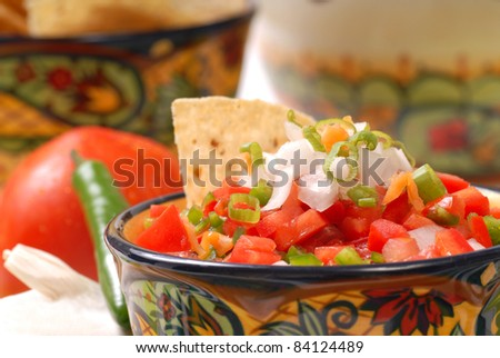 Fresh spicy salsa with tortilla chips along with the ingredients for the salsa - stock photo