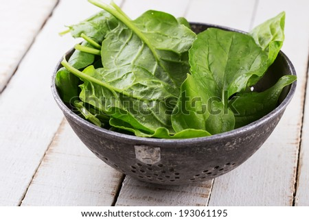 Fresh spinach in old bowl on white wooden background. Selective focus, horizontal.