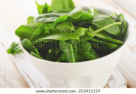 Fresh spinach leaves in white bowl. Selective focus
