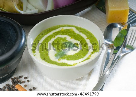 fresh spinach soup on a white bowl with sage and cream on top - stock photo