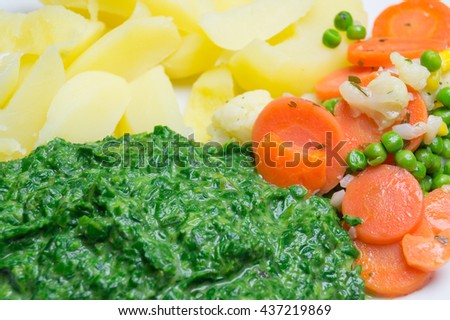 Fresh spinach with potatoes carrots and peas.
