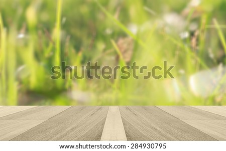 fresh spring grass with green bokeh and sunlight and wood floor. Beauty natural background - stock photo