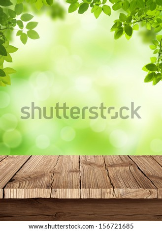 Fresh spring green bokeh background with wooden table for your products displays.. Beauty natural background. - stock photo