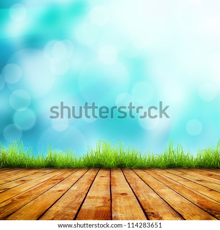 Fresh spring green grass with blue bokeh and sunlight and wood floor. Beauty natural background - stock photo