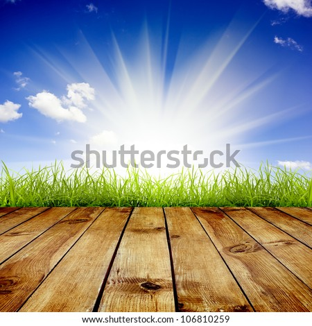Fresh spring green grass with blue sky and sunlight and wood floor background - stock photo