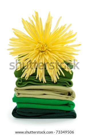 Fresh spring laundry. Yellow flower on top of green folded clothes.