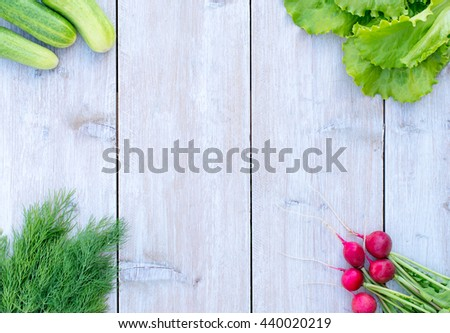 fresh spring lettuce, green onions and dill , cucumbers and radishes on a light wooden background fresh juicy green , spring green vegetables , vitamin salad, green dill , top view , space for text - stock photo