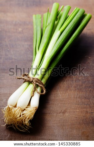 fresh spring onions on a wooden board