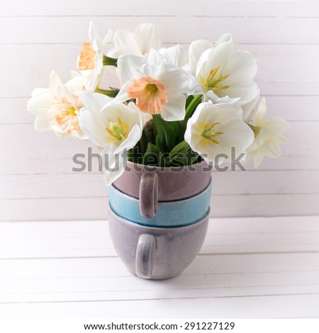 Fresh spring  pink daffodils  and white tulips flowers in vase  on white wooden planks. Selective focus. Square image. - stock photo