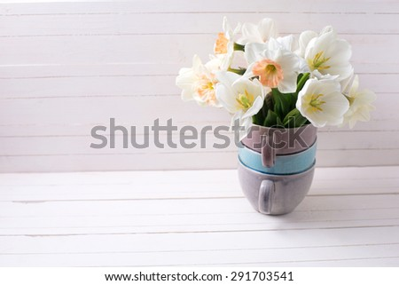 Fresh spring  pink daffodils  and white tulips flowers in vase  on white wooden planks. Selective focus. Place for text. - stock photo