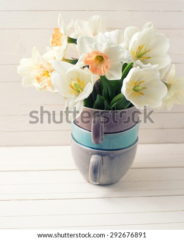 Fresh spring  pink daffodils  and white tulips flowers in vase  on white wooden planks. Selective focus.  Toned image. - stock photo