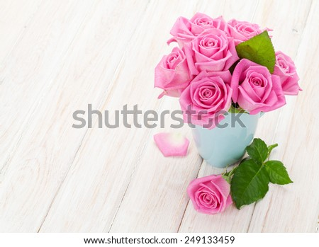 Fresh spring pink roses bouquet on white wooden table with copy space - stock photo