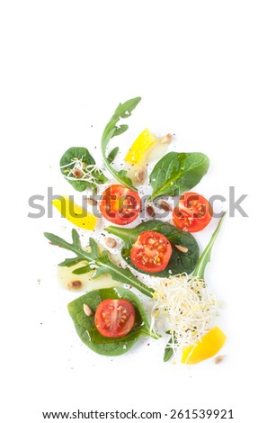 Fresh spring salad - modern artistic composition. Cherry tomatoes, yellow pepper, arugula, lambs lettuce, sunflower seeds and sprouts on white background from above. Layout with free text space. - stock photo
