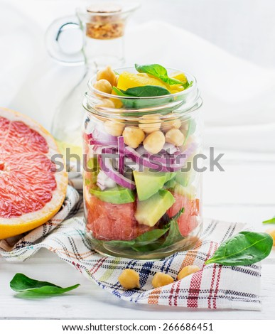 Fresh spring salad of grapefruit, avocado, sweet onion, spinach and chickpeas in a glass jar for a snack with you. The concept of healthy proper nutrition for the whole family. selective Focus - stock photo
