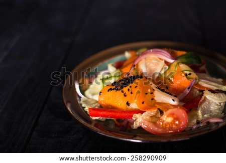 Fresh spring salad with carrot, red onion, tomato, cucumber, red sweet pepper, iceberg lettuce and black sesame on black wooden background. - stock photo