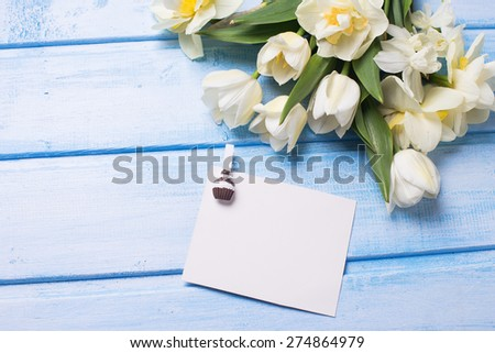 Fresh  spring white tulips and narcissus flowers  and empty tag on blue  painted wooden background. Selective focus. Place for text. Square image. - stock photo