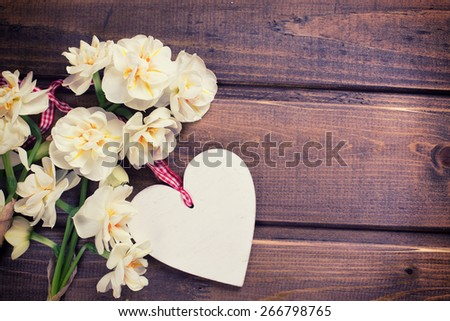 Fresh  spring yellow narcissus flowers and decorative  heart  on brown  painted wooden background. Selective focus. Place for text. Toned image. - stock photo