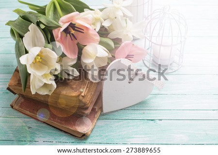 Fresh  spring yellow tulips and narcissus flowers on old books, decorative heart, candles in bird cages  in ray of light on turquoise  painted wooden background. Selective focus. - stock photo