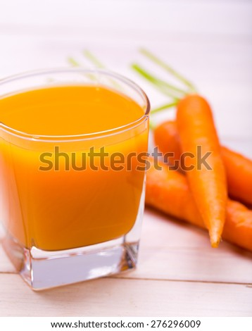 Fresh-squeezed carrot juice on wooden background - stock photo