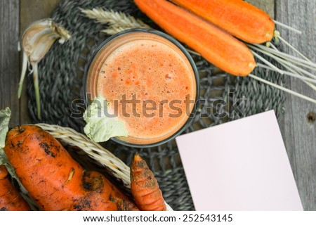 Fresh-squeezed carrot juice on wooden background. Black and white - stock photo