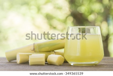 Fresh squeezed sugar cane juice in glass with cut pieces cane on nature background - stock photo