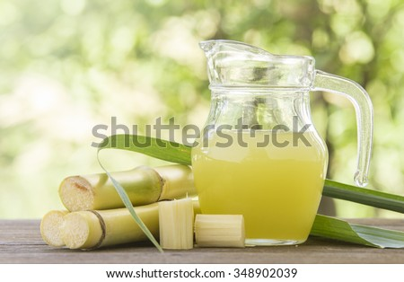 Fresh squeezed sugar cane juice in pitcher with cut pieces cane on nature background - stock photo