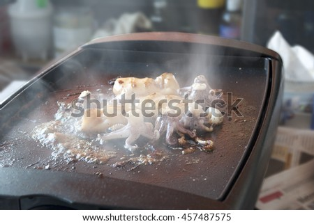 Fresh squid drill on electric heater. - stock photo