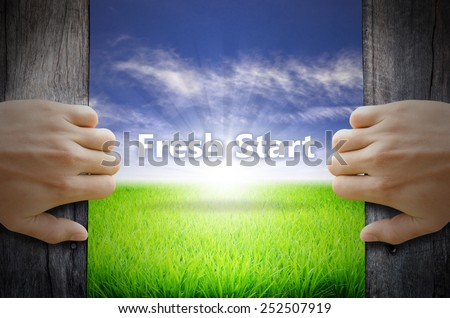 Fresh Start motivational word. Hand opening an old wooden door and found a texts floating over green field and bright blue Sky Sunrise. - stock photo