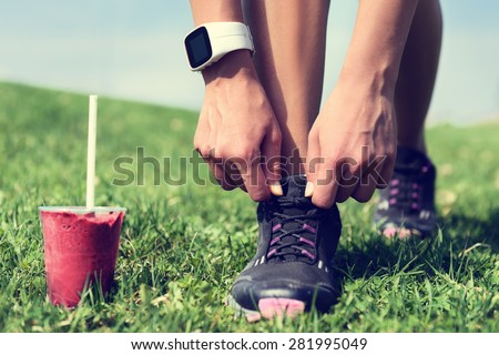 Fresh start on weight loss - runner tying laces with fruit smoothie wearing smartwatch for cardio. Detox, clean eating and diet. Woman getting ready for jogging workout. Closeup of running shoes. - stock photo