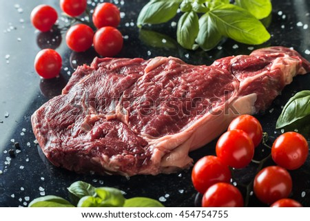 Fresh steak served with spices, tomatoes and leafs of basil on marble background. Uncooked beefsteak cooking on a kitchen. Delicious, spicy, juicy meat with copy space closeup.