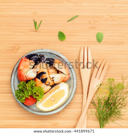 Fresh steamed red crabs leg in bowl. Fennel, parsley, rosemary, lemon and mint with fork on wooden cutting board. - stock photo