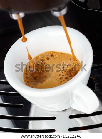 Fresh steaming espresso coffee being made - stock photo