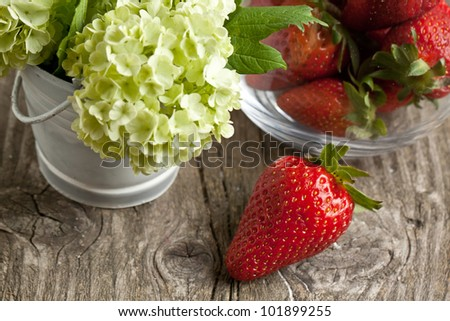 Fresh strawberries and bunch of flowers on old wooden table - stock photo