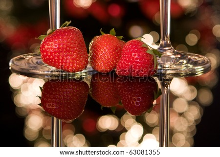 Fresh strawberries and champagne glasses in front of a blurred christmas tree - stock photo