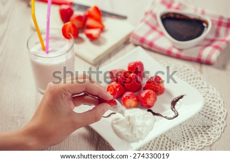 Fresh strawberries and whipped cream on a plate, fondant bitter chocolate in a bowl. Drink smoothies summer strawberry.Female hand holding strawberries - stock photo