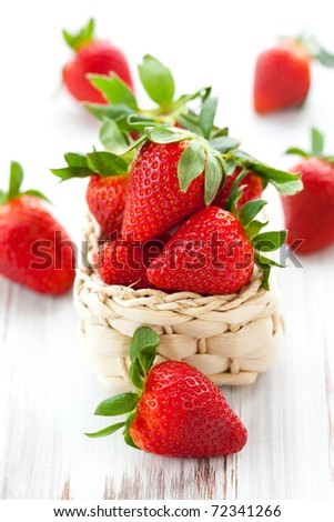 fresh strawberries in a basket on a white wooden table - stock photo