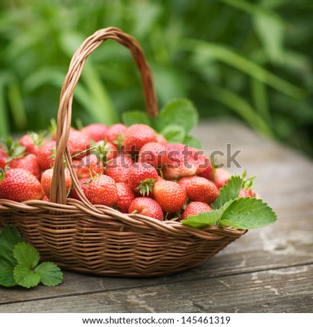 Fresh strawberries in a basket on old wooden table, selective focus - stock photo