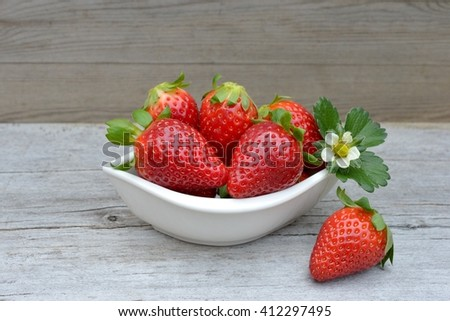 Fresh strawberries in a bowl on wooden table.