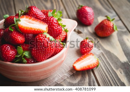 Fresh strawberries in a bowl on wooden table with low key scene. - stock photo
