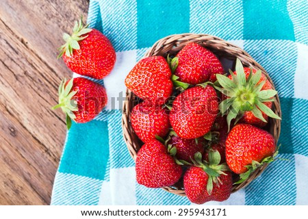 fresh strawberries in a bowl with checkered napkin on old wooden background - stock photo