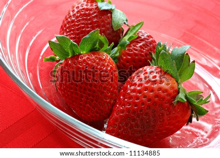 Fresh strawberries in a crystal dish over red tablecloth.  Tilted comp and sunlit patterns in the glass create an abstract effect.  Macro with shallow dof - stock photo