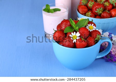 Fresh strawberries in a cup, a bowl with chamomile on a wooden background