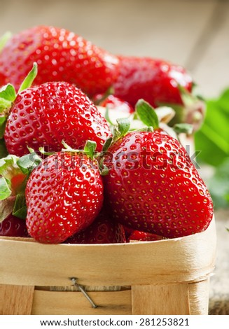 Fresh strawberries in a wicker basket on lerevyannom background, selective focus - stock photo