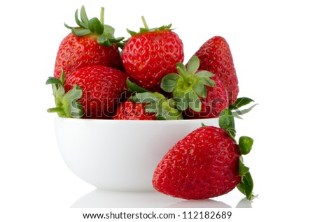 Fresh strawberries in bowl on white reflective background. - stock photo