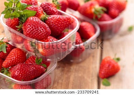 Fresh strawberries in containers and mint leaves on wooden table. - stock photo