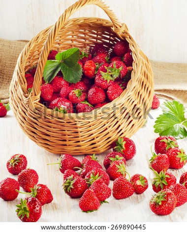 Fresh strawberries in the basket on a wooden table. - stock photo